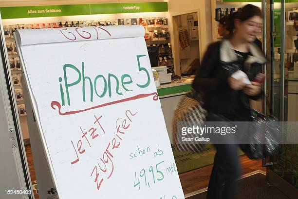 A young woman walks out of a shop advertising the new Apple iPhone 5 on the first day the smartphone went on sale on September 21 2012 in Berlin...