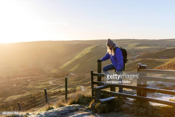 A young woman walks over a stile at sunrise in the Peak District National Park, England.