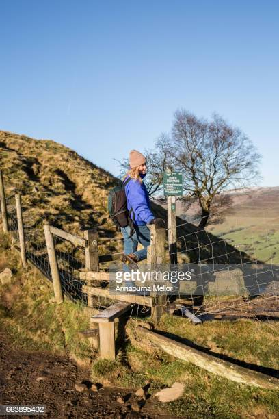 A young woman walks over a stile in the Peak District National Park in England.