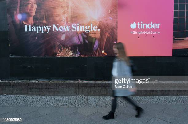 Young woman walks past a billboard advertisement for the dating app Tinder on February 18, 2019 in Berlin, Germany. Tinder has emerged as one of the...