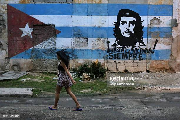 A young woman walks past a mural dipicting Cuban revolutionary leader Che Guevarra in the Jesus Maria neighborhood January 24 2015 in Havana Cuba...