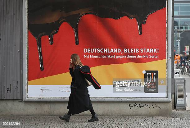 A young woman walks past a poster showing the German flag with a dripping black portion and that reads 'Germany stay strong With humanity against...