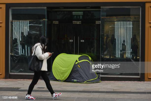 Young woman walks past a rough sleeper's tent on Grafton Street in Dublin city center during Level Five Covid-19 lockdown. On Monday, March 1 in...
