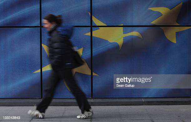 Young woman walks past a wall decorated with the flag of the European Union outside one of the buildings of the European Commission on November 17,...