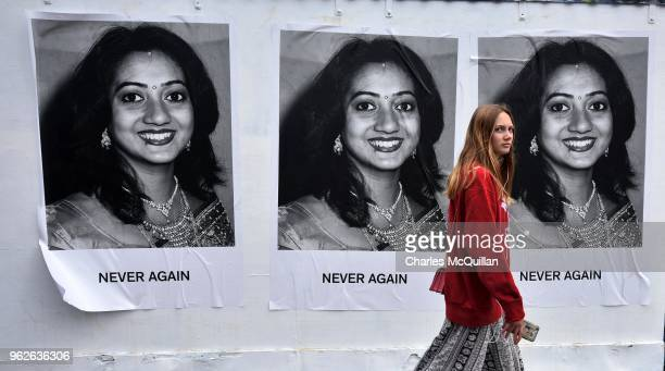 A young woman walks past art work featuring Savita Halappanavar which states 'Never Again' as the results in the Irish referendum on the 8th...