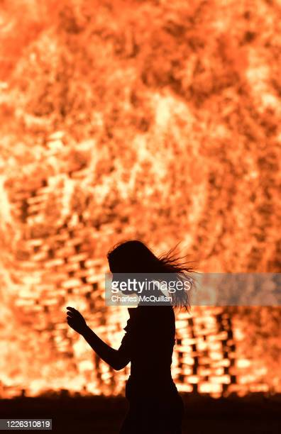 A young woman walks past the lit bonfire at the Ballycraigy estate 11th night bonfire on July 11 2020 in Antrim Northern Ireland Loyalists...