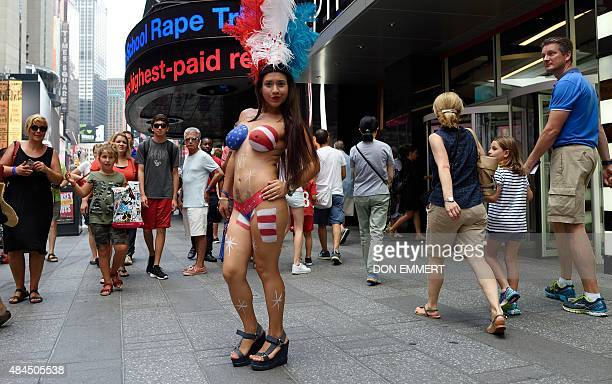 A young woman walks through Times Square amongst the crowd wearing body paint to cover herself August 19 2015 in New York Mayor Bill de Blasio said...