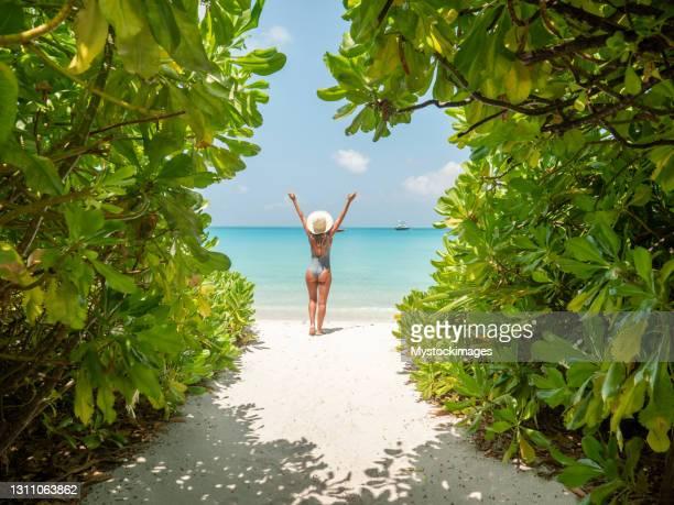 young woman walks towards beautiful beach - human arm stock pictures, royalty-free photos & images