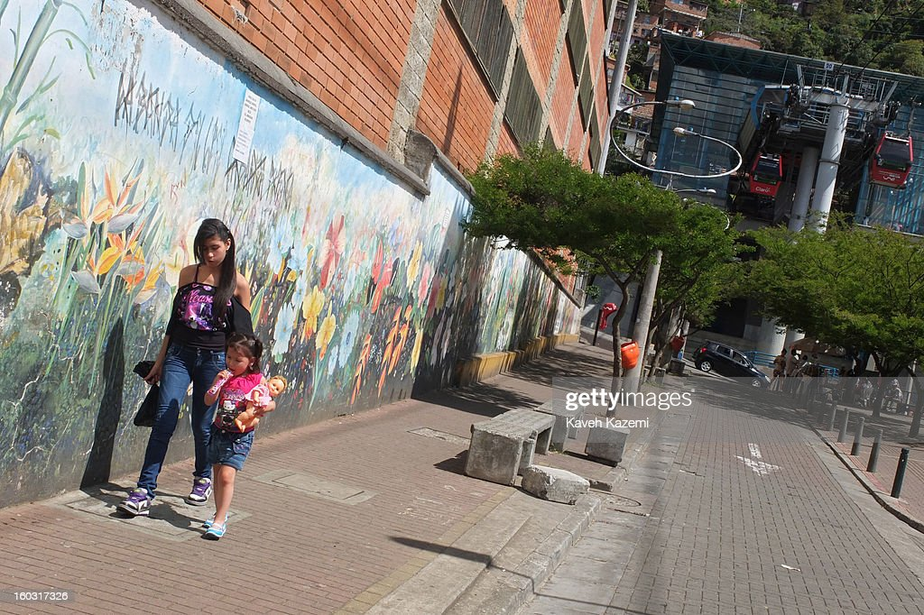 A young woman walks with a child past a mural painted by locals on a street in the city slums on January 5, 2013 in Medellin, Colombia. The notorious slums of Medellin have gone through urban and educational projects to improve the quality of life for its residence.