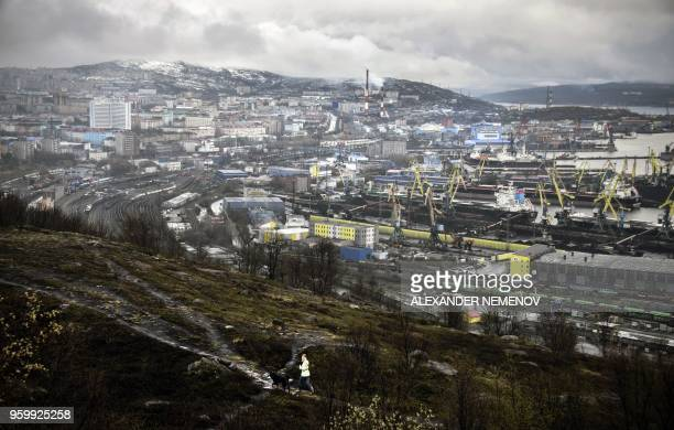 A young woman walks with a dog in front of the panorama of the Russian northern port city of Murmansk on May 18 2018 Akademik Lomonosov the worlds so...