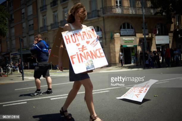 A young woman walks with a placard reading 'Human being different from finance' A quotmaree populairequot demonstration was called by more than 60...