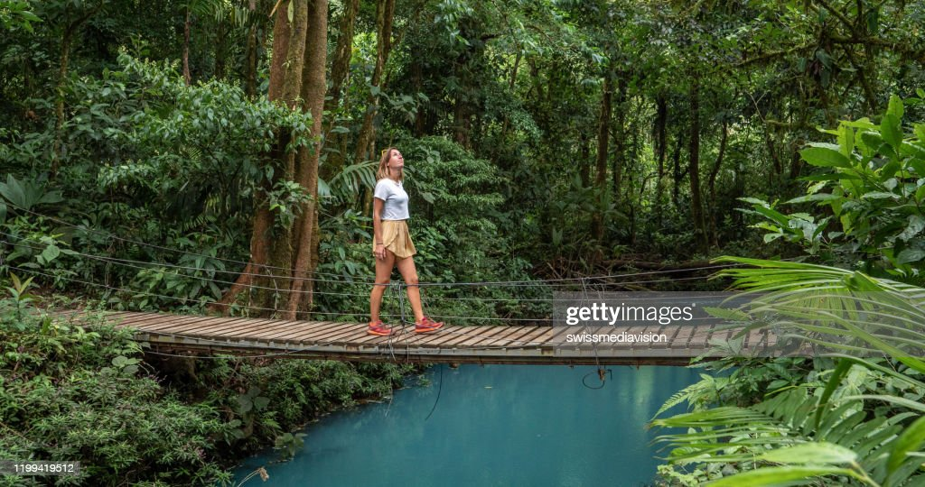 Young woman wandering in tropical rainforest walking on bridge over turquoise lagoon : Stock Photo