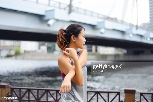 young woman warming up before her evening run - 練習 ストックフォトと画像