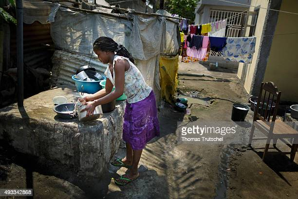 A young woman washes dishes in a slum in the city area from Beira on September 28 2015 in Beira Mozambique