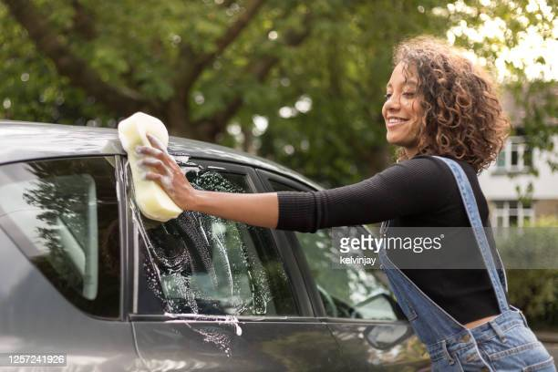 young woman washing car on driveway - washing stock pictures, royalty-free photos & images