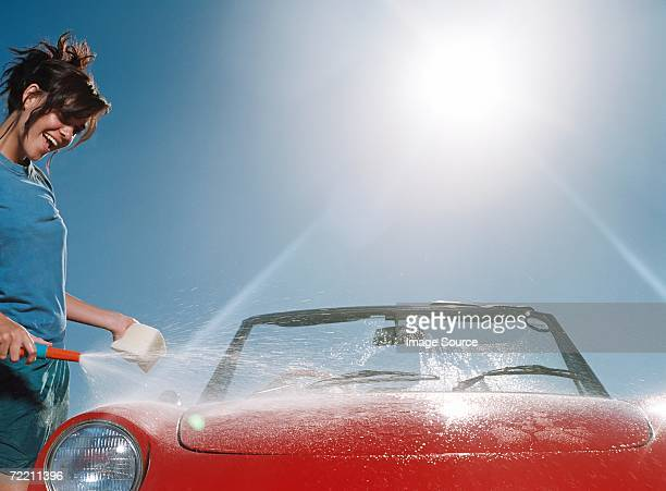 young woman washing car - red tube top stock photos and pictures