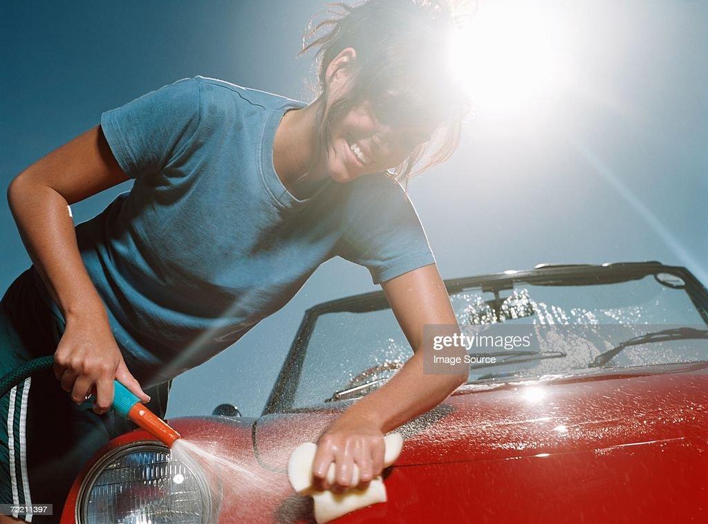 Young woman washing car : Stock Photo