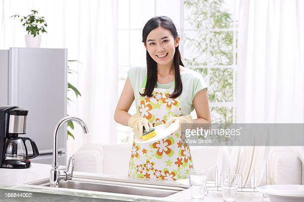 Young woman washing dishes in kitchen