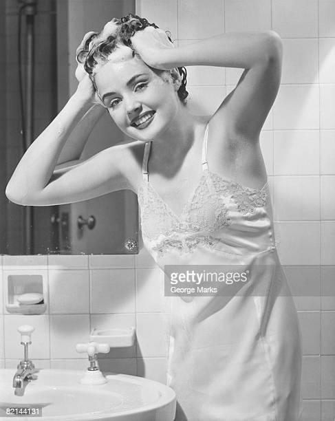 Young woman washing hair at bathroom sink, (B&W), portrait