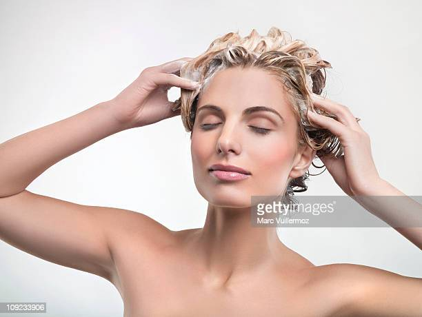 young woman washing hair - shampoo stock-fotos und bilder