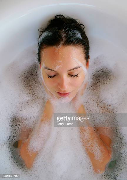 young woman washing her face in bath with bubbles