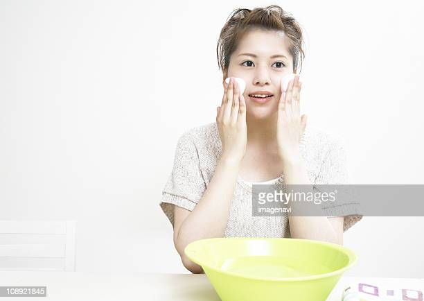 A young woman washing her face