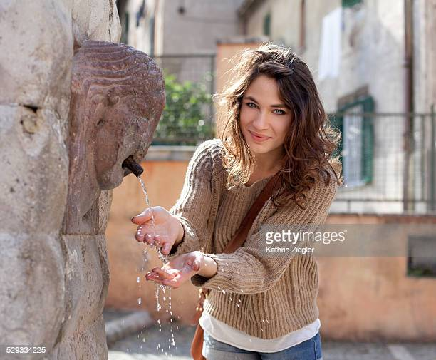 young woman washing her hands at Roman fountain