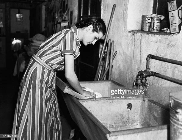 young woman washing tray  - number of people stock pictures, royalty-free photos & images