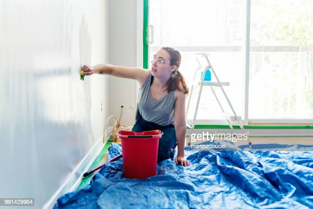 Young woman washing walls before painting them.