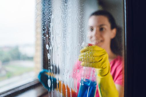Young woman washing window 1055221704