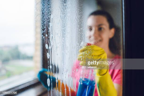 young woman washing window - clean stock pictures, royalty-free photos & images