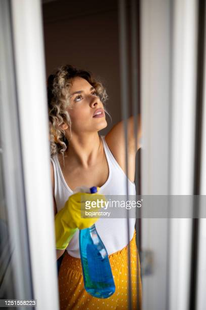 young woman washing window - washing up glove stock pictures, royalty-free photos & images