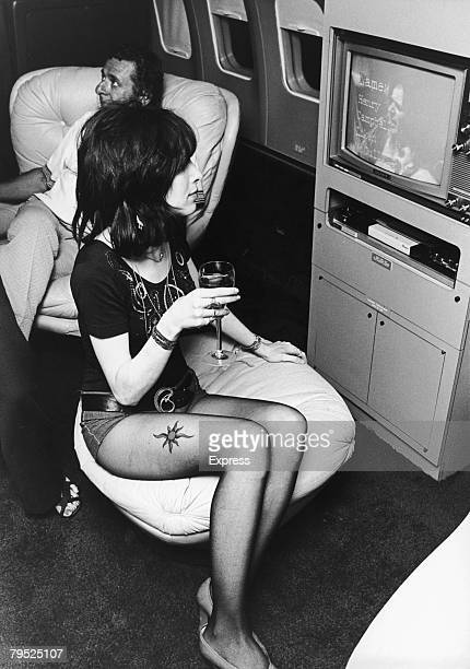 A young woman watches a video on board a private Boeing 720B airliner known as 'The Starship' which is being used by English rock group Led Zeppelin...