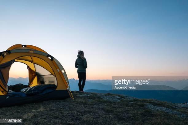 de jonge vrouw let op zonsopgang buiten het kamperen tent - heldere lucht stockfoto's en -beelden