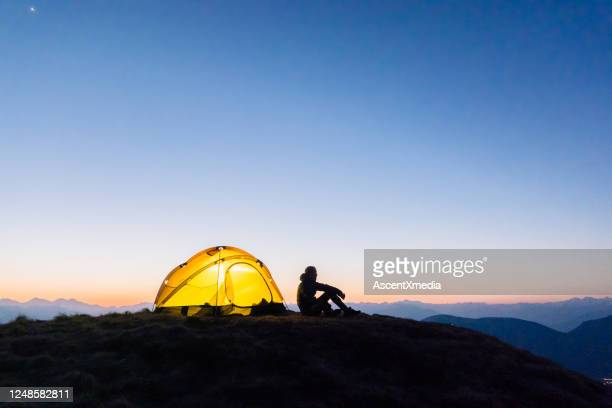 young woman watches sunrise outside camping tent - simple living stock pictures, royalty-free photos & images
