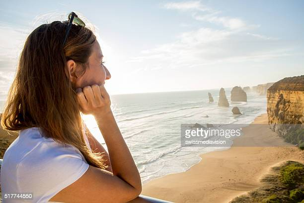 Young woman watches the sunset at the Twelve Apostles