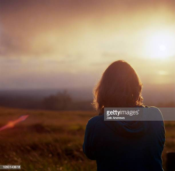 A young woman watches the sunset in Hawaii