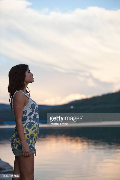 Young woman watches the sunset over the lake in Idaho.