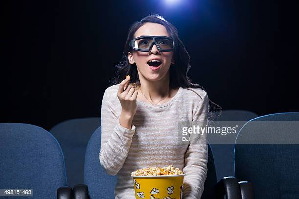 Young woman watching 3D movie in cinema