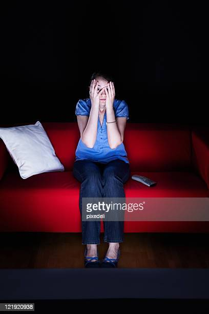 young woman watching a horror movie - horror movie stock photos and pictures