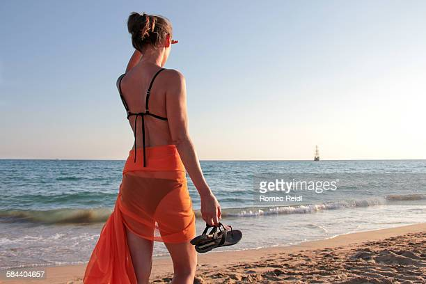 young woman watching a ship in the distance - thong bikini stock pictures, royalty-free photos & images