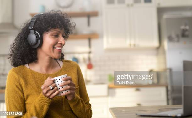 young woman watching a video on her laptop and listening podcast on headphones - weekend activities stock pictures, royalty-free photos & images