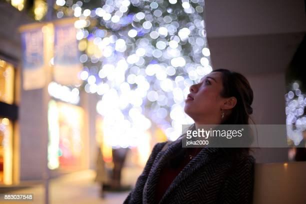 クリスマス イルミネーションを見て若い女性