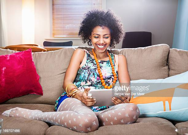 young woman watching digital tablet in livingroom. - black women wearing pantyhose stock pictures, royalty-free photos & images