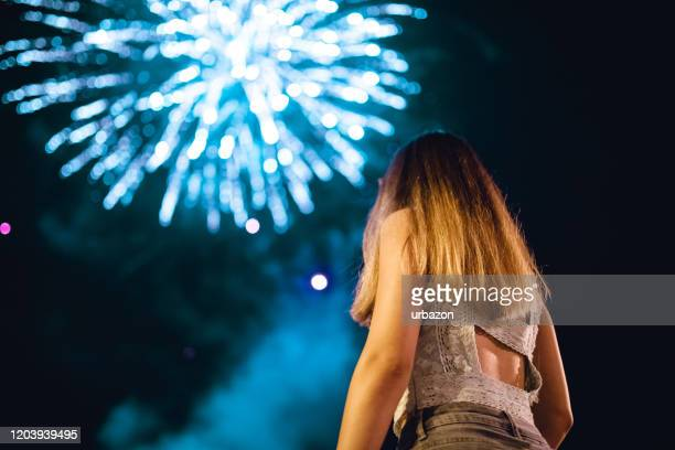 young woman watching fireworks - strap stock pictures, royalty-free photos & images