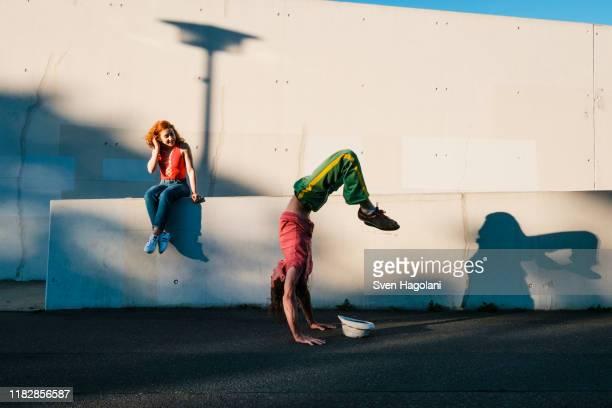young woman watching man do handstand along urban wall - leben in der stadt stock-fotos und bilder