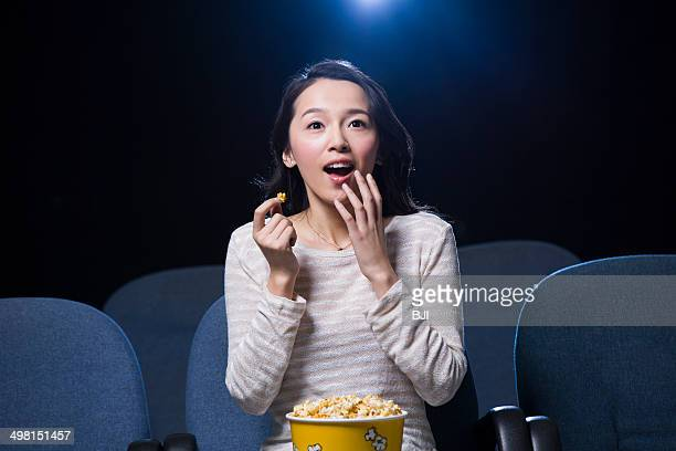 Young woman watching movie in cinema with popcorn in hand