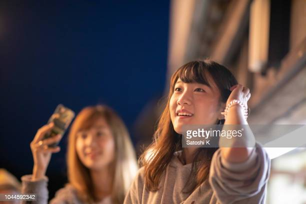 young woman watching night parade in traditional japanese festival - entertainment event stock pictures, royalty-free photos & images