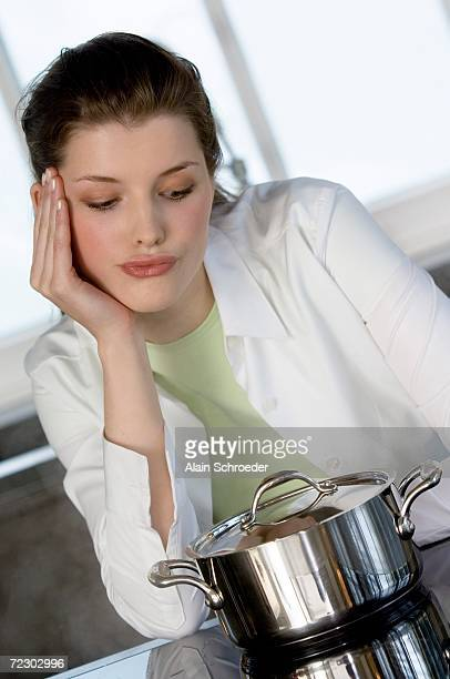 Young woman watching over saucepan on vitroceramic hob