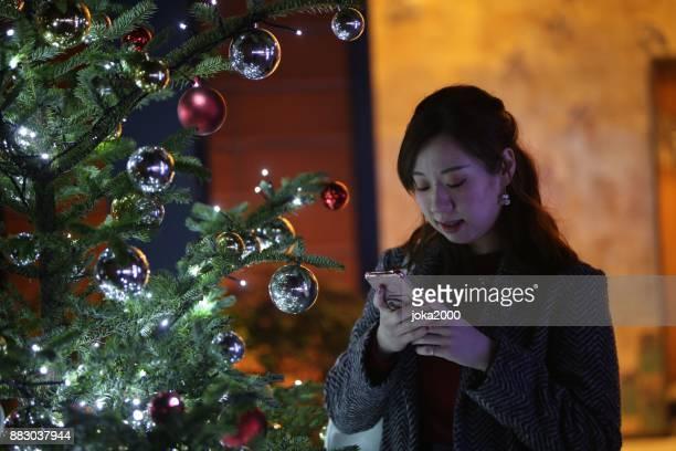 クリスマス ツリーの横に携帯電話を見ている若い女性